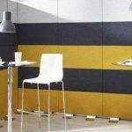 Tabique hecho con módulos de acondicionamiento acústico Divi Put On, en color negro, gris y amarillo, para crear un espacio separado con mesas en un entorno de oficina. Clase absorción de ruido A